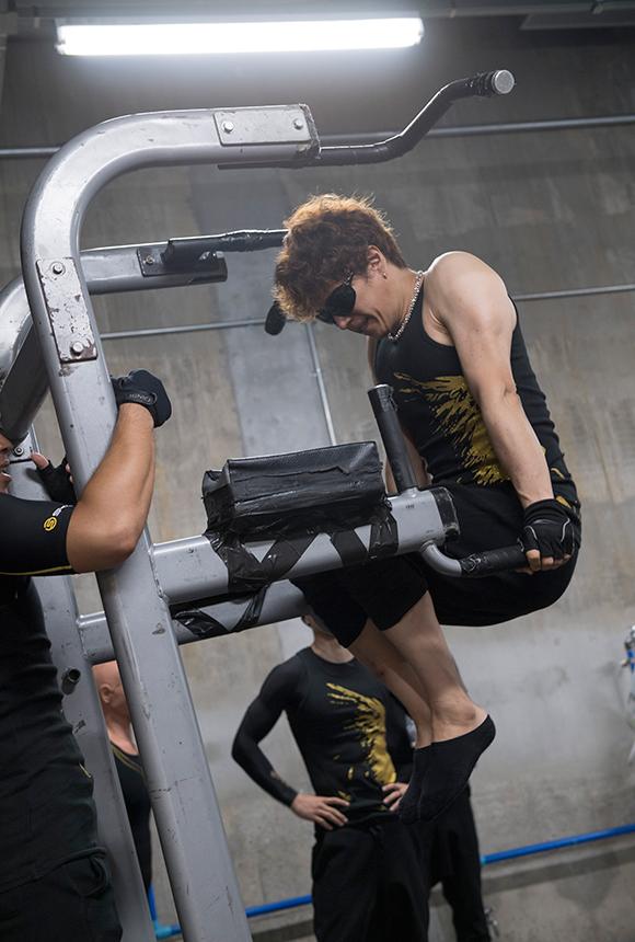 """一見すると普通のディップスのようだが、膝を曲げて背筋を使わず、腕の上腕三頭筋を最大伸張から最大収縮させるGACKT独自の""""ゼロ筋""""のトレーニング。"""