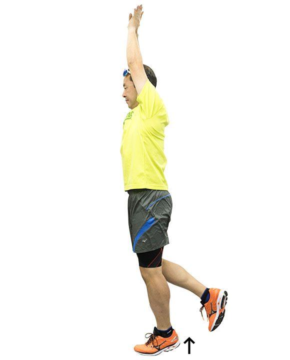 さらに重心を上に移動させるトレーニングその2。両手を頭上に引き上げて、片脚立ち&軸脚の踵上げ。