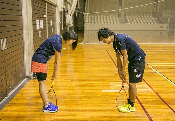 足の間にラケットを挟み、床と垂直に立てる。利き腕を胸の前に伸ばし、握手をするように手のひらを内側に向け、そのままラケットを握る。